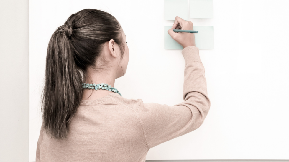 Girl writing perfectly on one of 4 squares on a white board