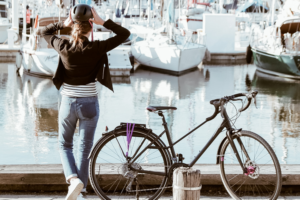 Girl adjusting her bicycle helmet, while looking out over water at sailboats