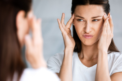 Woman looking into a mirror with her hands on her temples making an worrisome face.