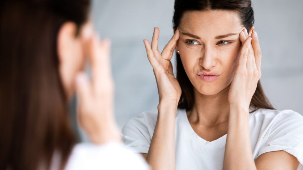 Woman looking into a mirror with her fingers on her temples because of the negative thoughts in her mind.