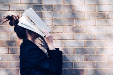 Woman side on, looking up with a open book over her face as a form of self-sabotage.