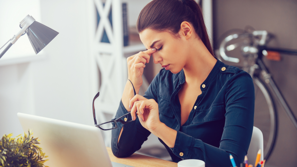 A woman sitting at her desk pinching the bridge of her nose trying to defuse the negative thoughts created by her inner critic