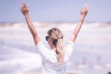 Woman standing with her arms in the air full of self-love